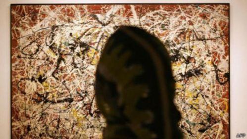 """Una iraní admira """"Mural sobre Terreno Rojo Indio"""" durante una exposiciòn en 2005."""